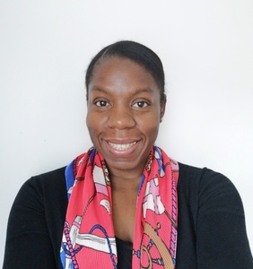 Yinka smiles at the camera, wearing a red patterned scarf