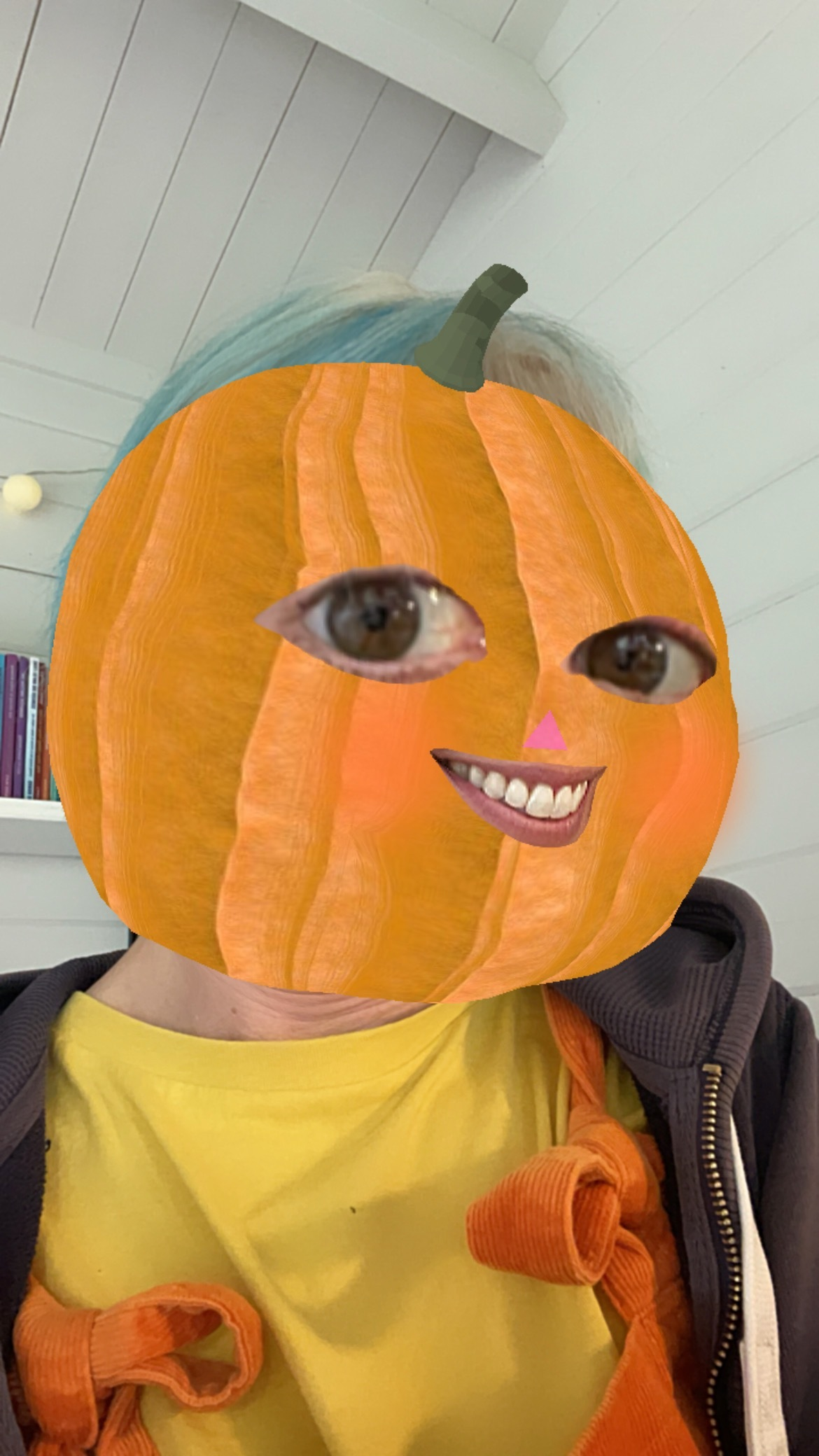 Vicky has a pumpkin head filter, yellow tshirt and orange dungarees